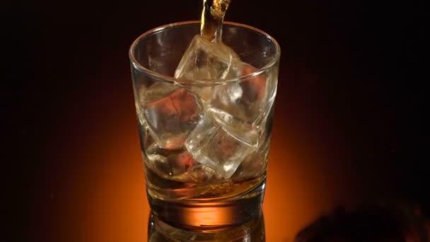 Egy pohár whisky bourbon a jégen, fényes háttéren