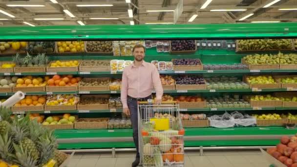 Pohledný muž s nákupní vozík v supermarketu