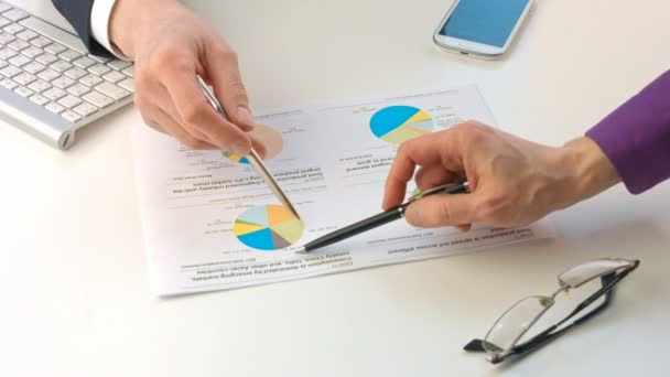 Male hands pointing at paper containing data about economic situation