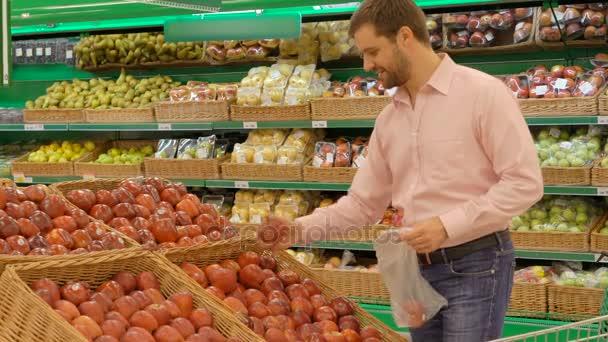 Muži výběr čerstvých červených jablek v obchodu s potravinami