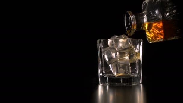 Whisky s ledem nalila z karafy rystal na černém pozadí kopie prostor