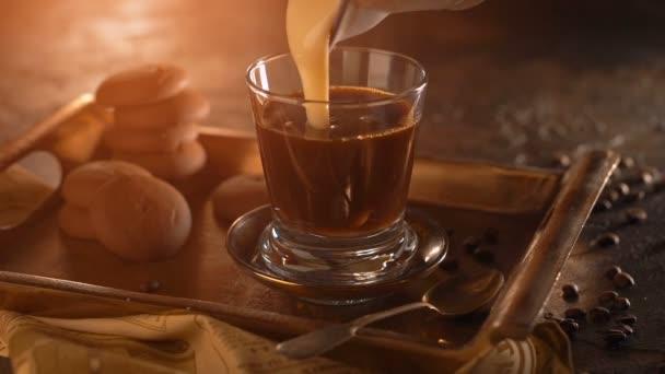 Kaffee in einem transparenten Glas. mit Kondensmilch auf Metallblech gießen