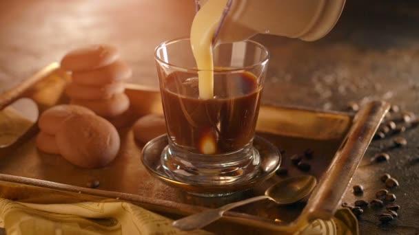 Kaffee in einem transparenten Glas. mit strömendem Kondensmilch auf Holztisch