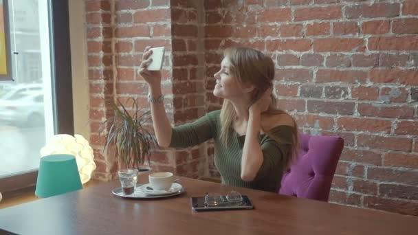 Mladá krásná žena s krásným úsměvem pózuje při fotografování se fotoaparát v mobilním telefonu