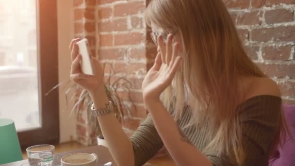 Young smiling woman having video conversation using smartphone during breakfast in coffee shop,