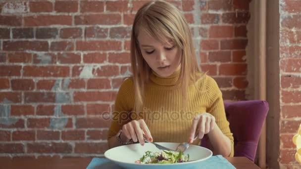 Roztomilý dívka jíst podrážděný salát v restauraci