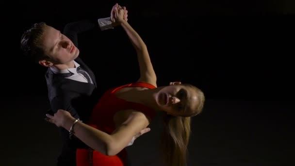 Professional dancers dancing in the studio on dark background