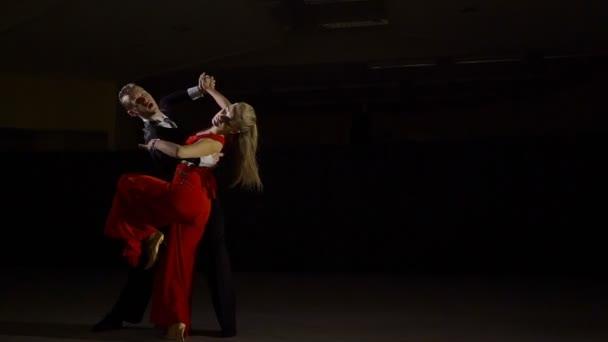 Young ballroom dance couple preform exhibition dance in studio