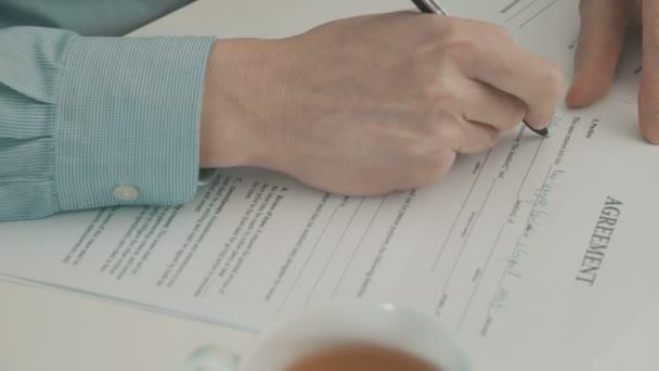 Hand des Geschäftsmannes füllt Partnerschaftsvertrag