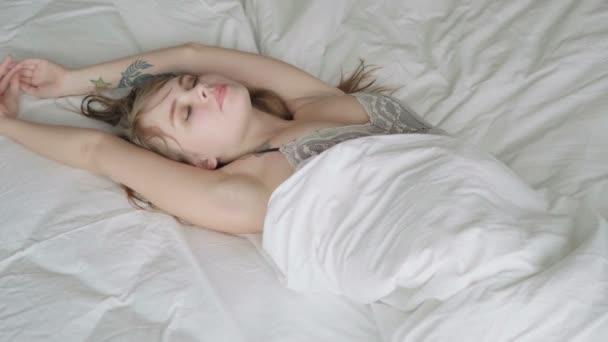 Mladá krásná smyslná žena leží na posteli