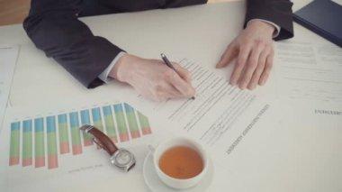 Hand of businessman filling partnership agreement