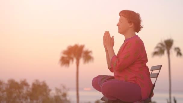 Frau in ethnische Kleidung praktiziert Yoga und im Lotussitz meditiert