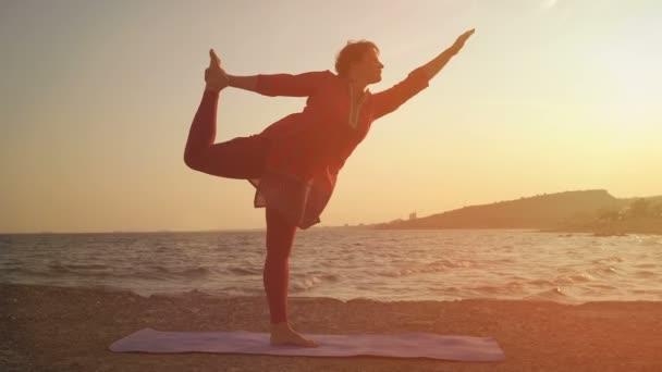 Jóga při západu slunce na pláži. žena provádějící jóga ásany