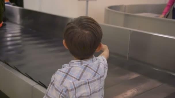 Chlapečka čeká na kufr na dopravní pás v zavazadel na letišti zavazadla