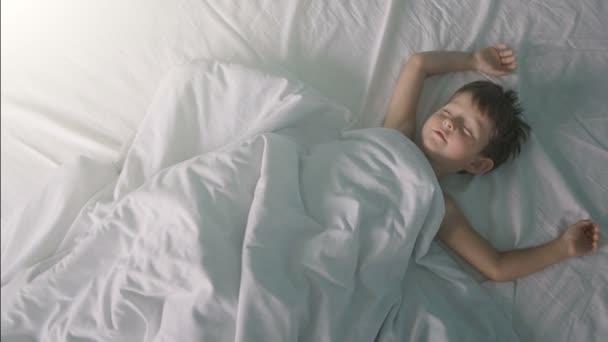 Malý chlapec, táhnoucí se v posteli po probuzení nahoru