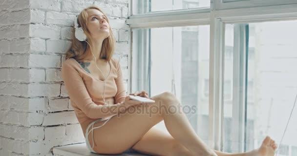 Szexi nő ül az ablakpárkányon, és használ smartphone fejhallgató otthon