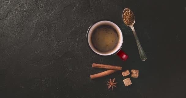 Cinemagrah loop. Coffee mug with cinnamon sticks on dark table. Top view with copy space