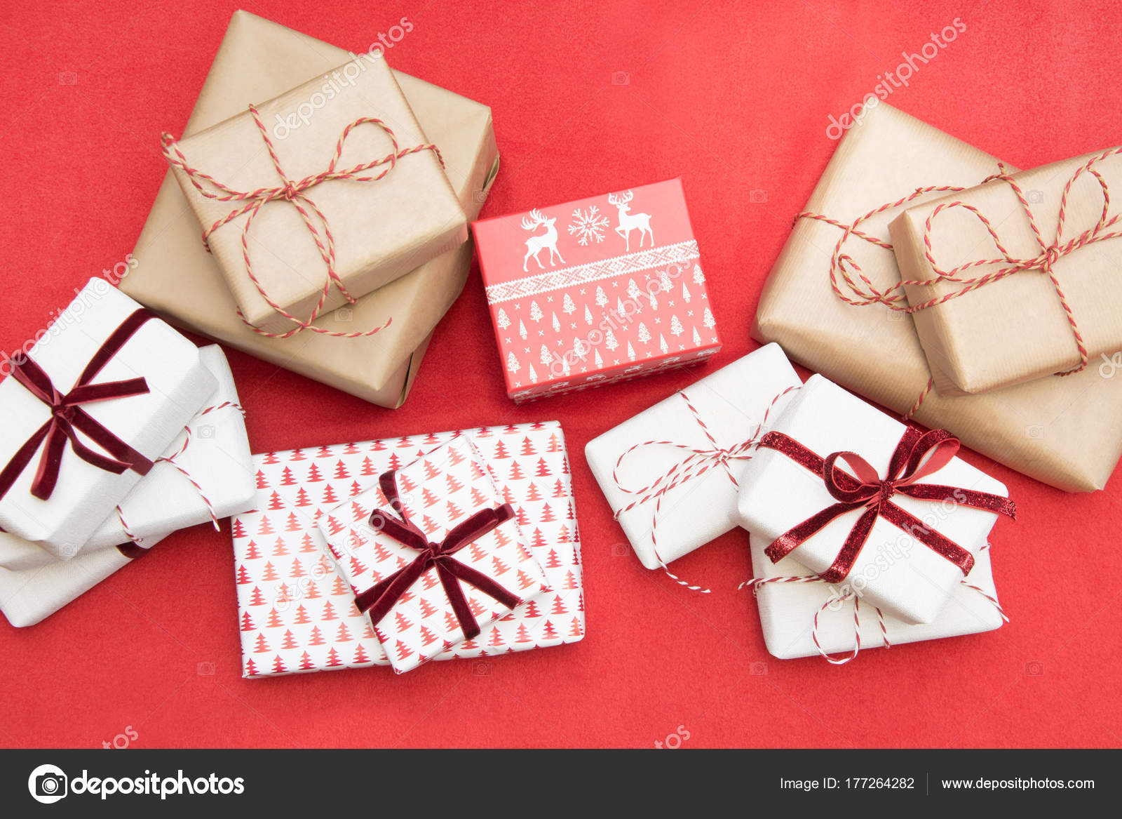 Christmas gifts wrapped in ornament paper and decorative red rope ...