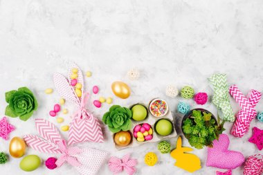 Frame border with easter decoration. Painted eggs in trays, candy, flowers, succulent with copy space. Spring background. Flat lay, top view