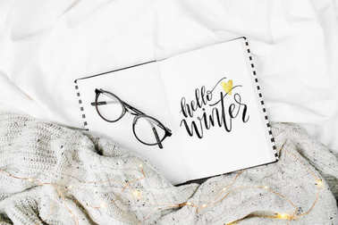 notebook with hello winter text on bed
