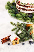 Gingerbread house with decorated fir branches and berries