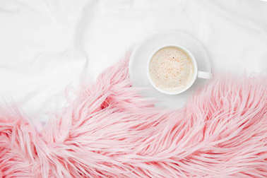 Top view of cup of coffee and pink fluffy fur plaid a pink fluffy fur plaid on bedding sheet