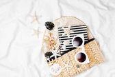 Plážová taška s sluneční brýle a doplňky v posteli, koncept dovolenou