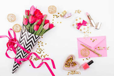 Pink and Gold Styled Desk with Florals. Pink tulips in black and white stylish wrapping paper, gifts, cosmetics and female accessories with confetti on white background