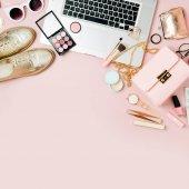 Módní blogger pracovní prostor s laptop a samice příslušenství, produkty kosmetiky na světle růžové tabulka. Plochá ležel, horní pohled
