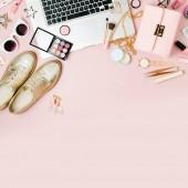 Fotografie Módní blogger pracovní prostor s laptop a žena doplňky, kosmetické produkty na světle růžové tabulka