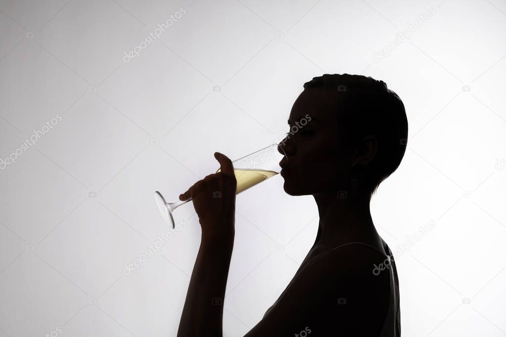 silhouette of woman with a short hair drinks champagne side face stock photo