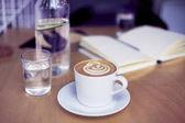 Šálek kávy cappucino, sklenice čisté vody, láhev na dřevěný stůl, bílého interiéru