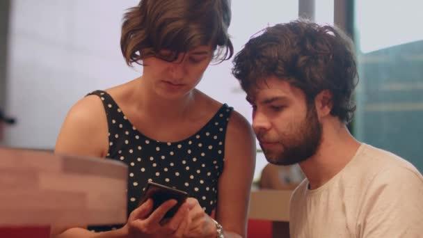 Egy fiatal pár valami alkalmazásról beszél egy kávézóban, ami az okostelefonra néz.