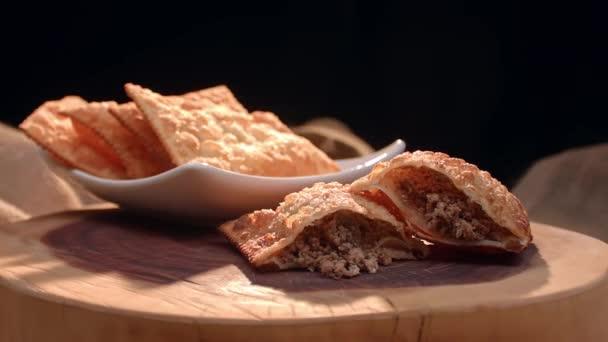 Smažené pečivo na talíři a masové těsto rozkrojené na dřevěné desce.
