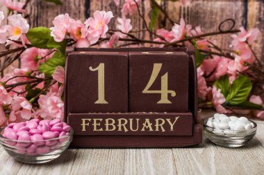 Wooden calender, candy and flowers.  Date is February 14 for Valentines concept