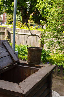 A well with a wooden frame, a crane-type lifting mechanism and a wooden bucket
