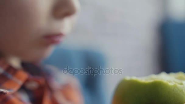 Little boy biting off apple