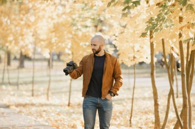 Bald brutal photographer with a beard in a suede leather jacket, blue shirt and jeans looking at photos on the camera in the park in the afternoon