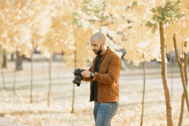 Bald brutal photographer with a beard in a suede leather jacket, blue shirt and jeans selects photos on the camera in the park in the afternoon