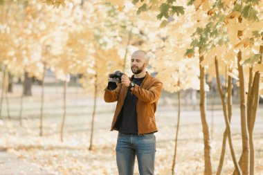 Bald brutal photographer with a beard in a suede leather jacket, blue shirt and jeans scrolls photos on the camera in the park in the afternoon