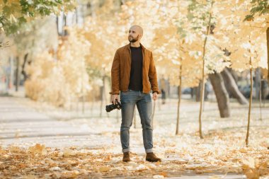 Bald stylish photographer with a beard in a suede leather jacket, blue shirt, jeans, and Chelsea boots holds the camera and looks for the best location in the park in the afternoon