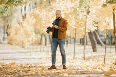 Bald stylish photographer with a beard in a suede leather jacket, blue shirt, jeans, and Chelsea boots holds the camera and looks for something in his smartphone in the park in the afternoon