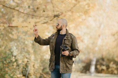 Bald photographer with a beard in aviator sunglasses with mirror lenses, olive cargo combat military jacket, blue shirt with digital wristwatch holds his camera and points a finger in the forest.