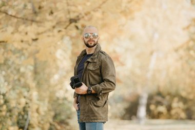 Bald photographer with a beard in aviator sunglasses with mirror lenses, olive cargo military jacket, blue shirt with digital wristwatch holds his camera and poses in the forest in the afternoon.