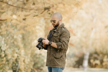 Bald photographer with a beard in aviator sunglasses with mirror lenses, olive cargo military jacket, blue jeans and shirt with digital wristwatch scrolls photos in the camera in the forest.