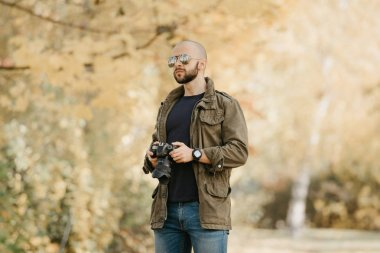 Bald photographer with a beard in aviator sunglasses with mirror lenses, olive military combat jacket, blue jeans and shirt with digital wristwatch holds the camera and looks straight in the forest.