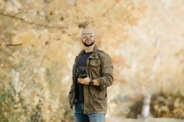 Bald photographer with a beard in aviator sunglasses with mirror lenses, olive military combat jacket, blue jeans and shirt with wristwatch poses holding his dslr camera and looks straight in the forest