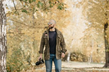 Bald photographer with a beard in aviator sunglasses with mirror lenses, olive military combat jacket, blue jeans and shirt with digital wristwatch holds the camera and goes straight in the park
