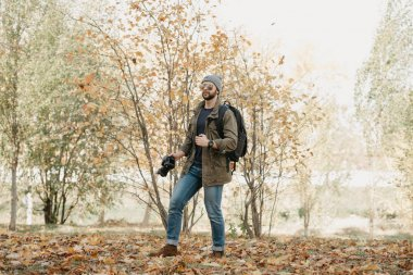 A brave traveler with a beard in aviator sunglasses with mirror lenses, olive military jacket, jeans with a backpack wristwatch holds the DSLR camera, looks around in the forest