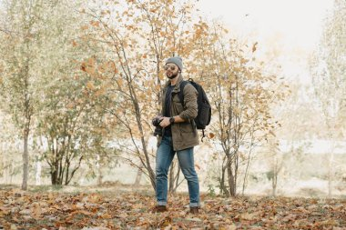 A photojournalist with a beard in aviator sunglasses with mirror lenses, olive military jacket, jeans, hat with a backpack with wristwatch holds the DSLR camera, looks around near the battlefield